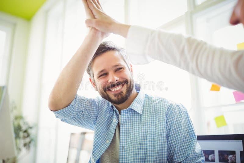 Glimlachende medewerkers die hoog-vijf in creatief bureau geven stock afbeeldingen