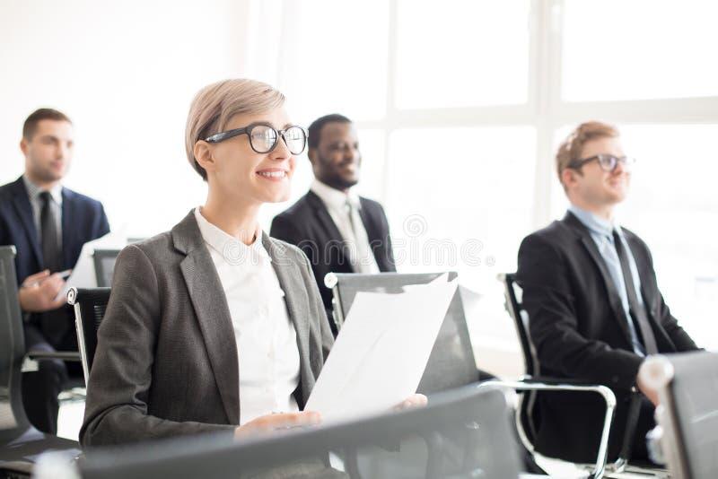 Glimlachende medewerkers die op seminarie zitten stock afbeelding
