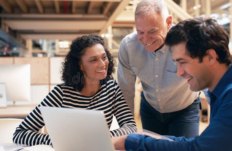 Glimlachende medewerkers die samen over laptop in een bureau spreken royalty-vrije stock foto