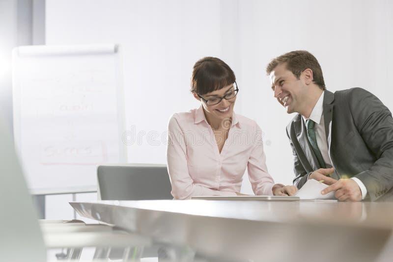 Glimlachende medio volwassen bedrijfscollega's die terwijl het zitten bij conferentielijst in bestuurskamer bespreken stock afbeeldingen