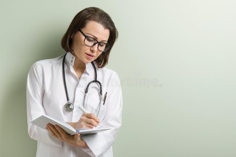 Glimlachende medische arts die nota's nemen stock foto