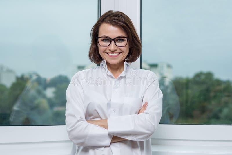 Glimlachende medische vrouw arts bij het Ziekenhuis, panoramisch venster als achtergrond royalty-vrije stock afbeeldingen