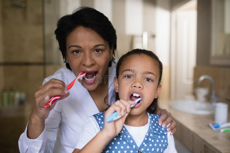 Glimlachende meisje en grootmoeder het borstelen tanden in badkamers stock foto's