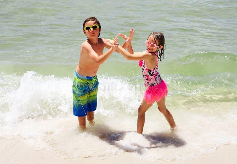 Glimlachende meisje en jongen die samen in water dansen stock afbeeldingen
