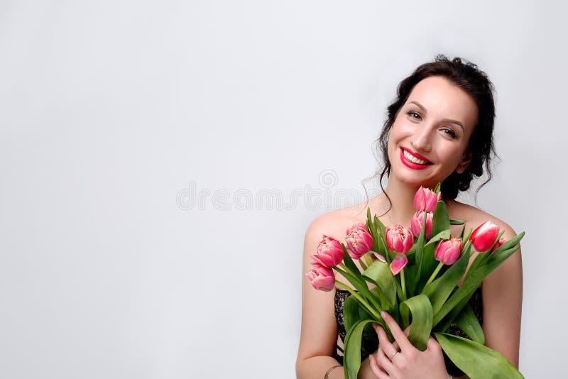 Glimlachende meisje en tulpen stock foto's