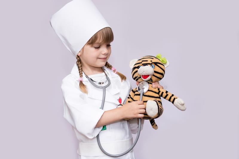 Glimlachende meisje speelarts en luisterteddybeer met stethoscoop stock afbeelding