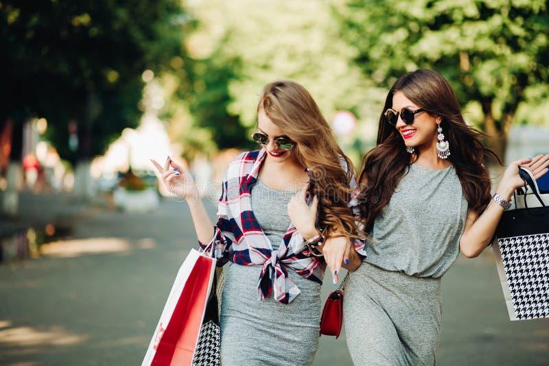Glimlachende meisjes die bij park na het shooping met documenten zakken lopen royalty-vrije stock afbeeldingen