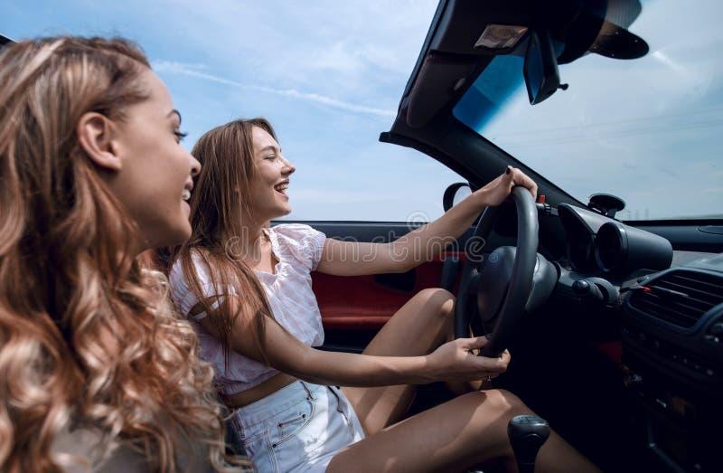 Glimlachende meisjes die in een convertibele auto reizen stock afbeeldingen