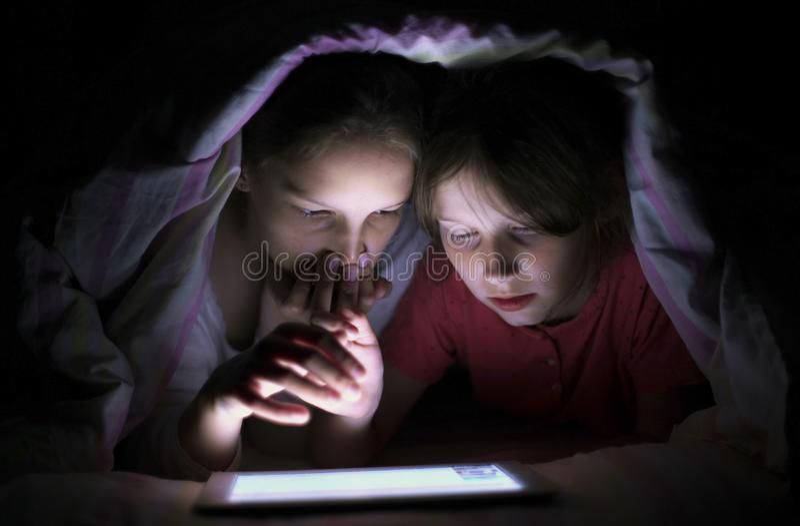 Glimlachende meisjes die tablet surfen onder deken bij nacht royalty-vrije stock fotografie