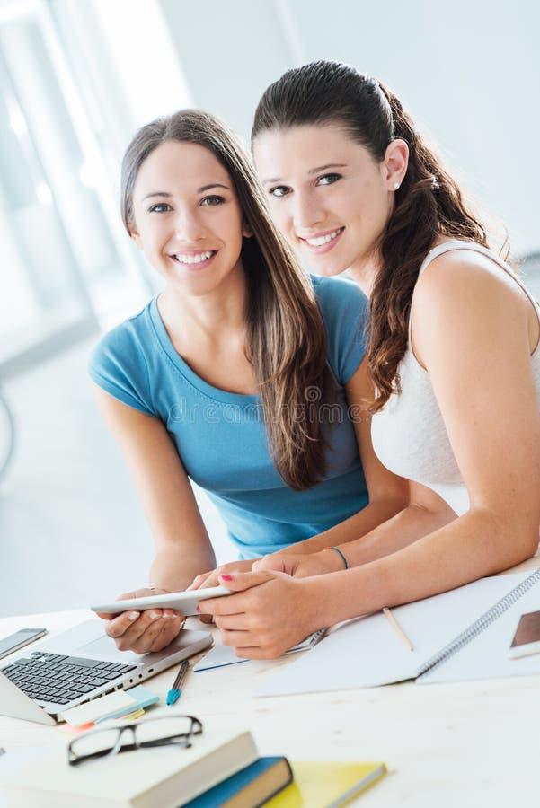 Glimlachende meisjes die thuiswerk thuis doen stock foto