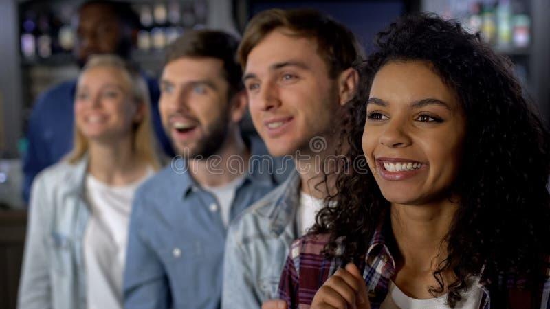 Glimlachende mengen-rasvrienden die voor team, het letten op wedstrijd, gebeurtenispubliek wortel schieten royalty-vrije stock foto