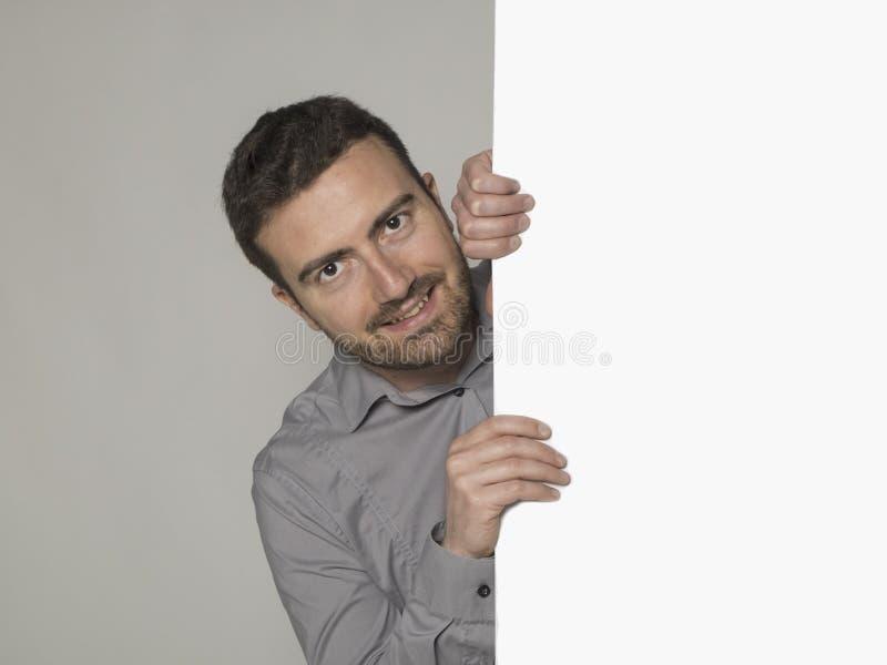 Glimlachende mens achter een groot kartel stock afbeelding