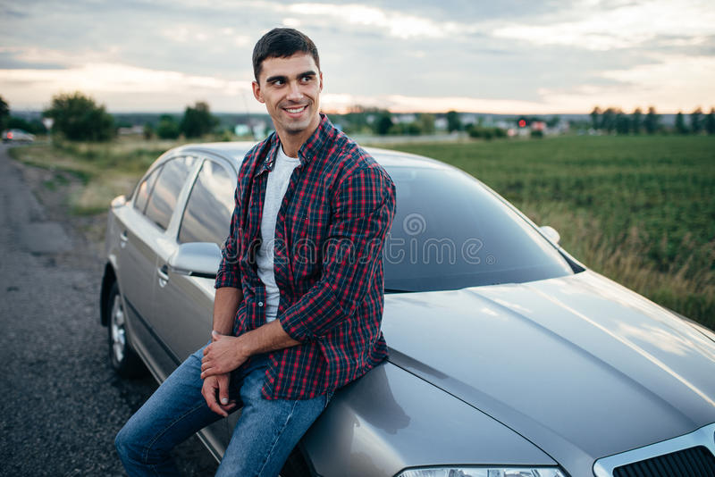 Glimlachende mens dichtbij zijn auto op kant van de weg in de zomerdag stock foto