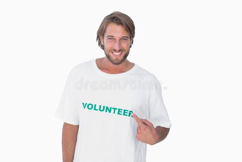 Glimlachende mens die aan zijn vrijwilligerst-shirt richten royalty-vrije stock fotografie
