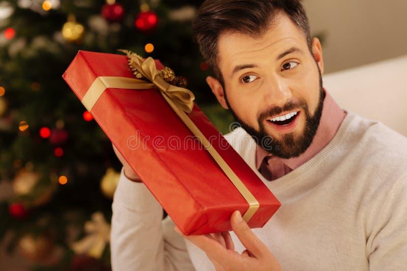 Glimlachende mens die binnenkant van giftdoos willen kennen stock fotografie