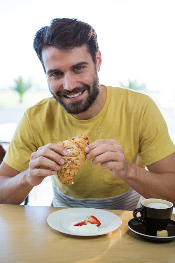 Glimlachende mens die croissant in koffiewinkel hebben stock afbeeldingen