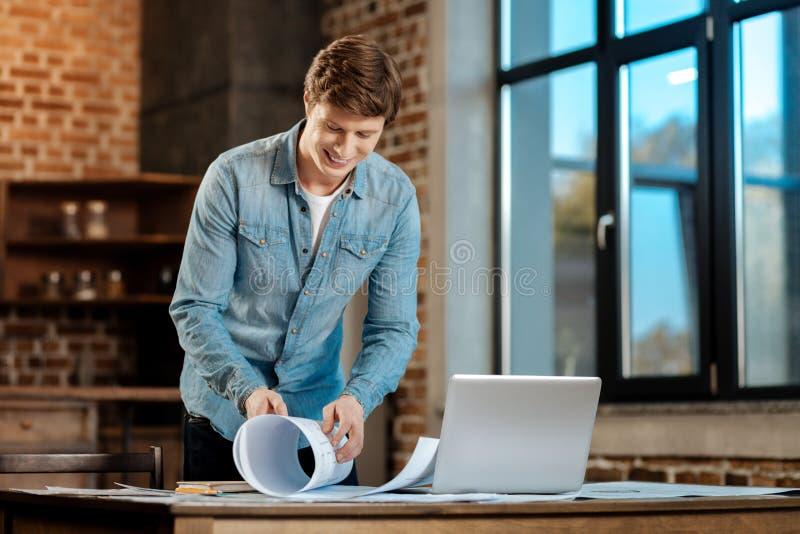 Glimlachende mens die een blauwdruk in de studie rollen royalty-vrije stock foto