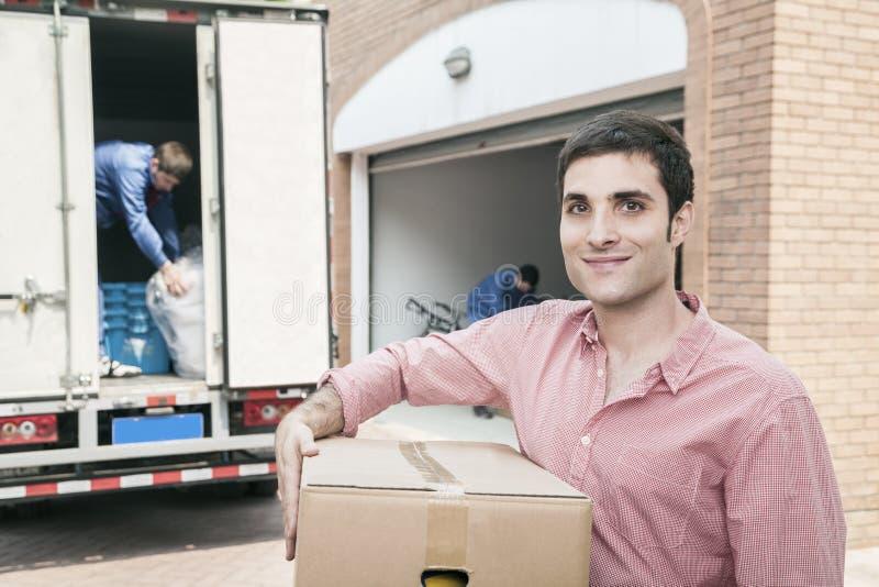 Glimlachende mens die een kartondoos houden en zich in zijn nieuw huis bewegen royalty-vrije stock afbeelding
