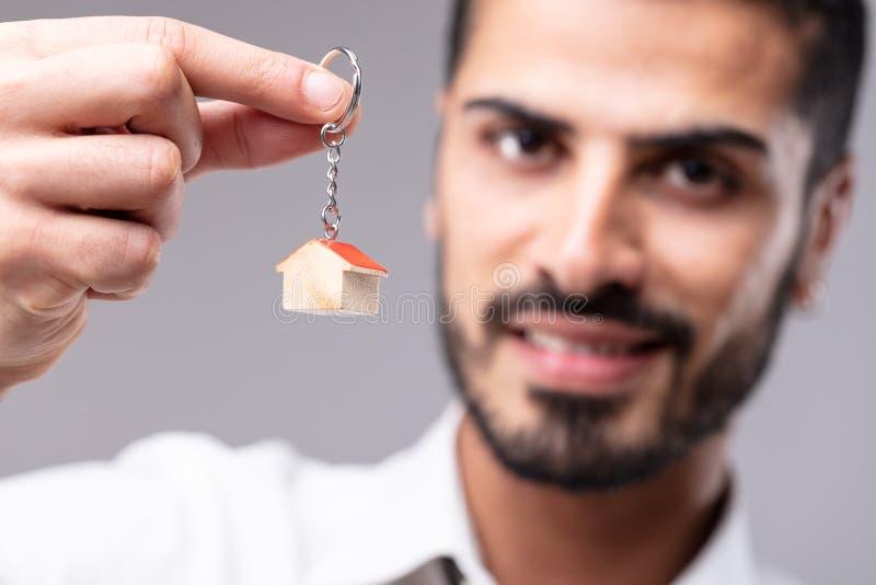 Glimlachende mens die een sleutelring met huis steunen royalty-vrije stock foto's