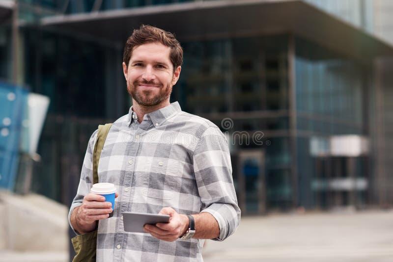 Glimlachende mens die een tablet gebruiken terwijl het lopen in de stad stock fotografie