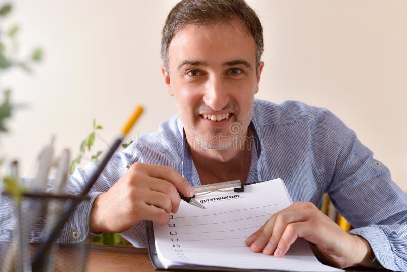 Glimlachende mens die een vragenlijst op een houten lijst tonen royalty-vrije stock afbeeldingen