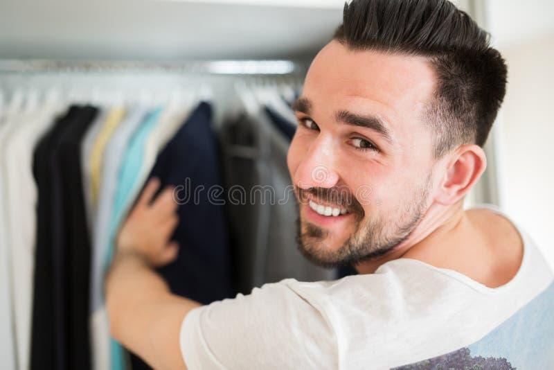 Glimlachende mens die kleren kiezen stock afbeelding