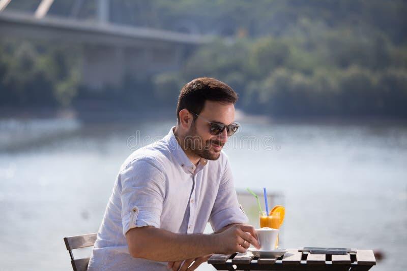 Glimlachende mens die in koffie in strand genieten van royalty-vrije stock fotografie