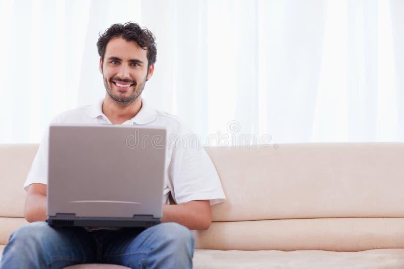 Glimlachende mens die laptop met behulp van royalty-vrije stock afbeeldingen