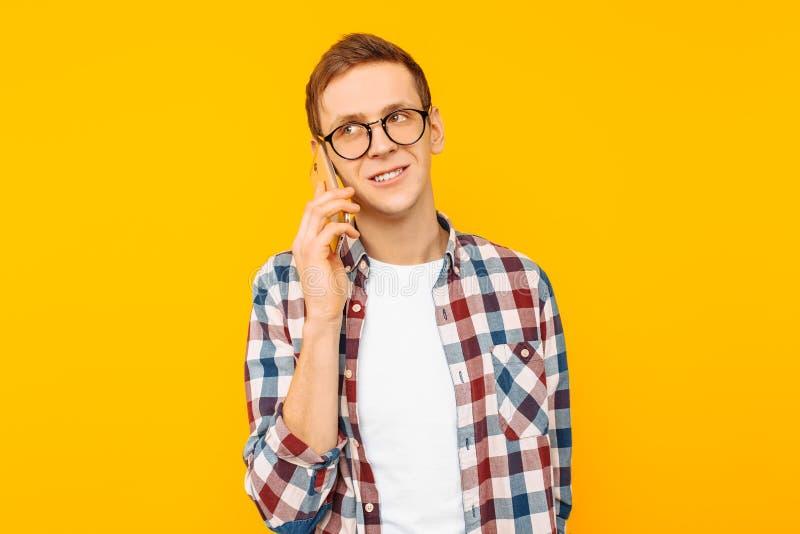 Glimlachende mens die op de telefoon, op een gele achtergrond spreken stock fotografie