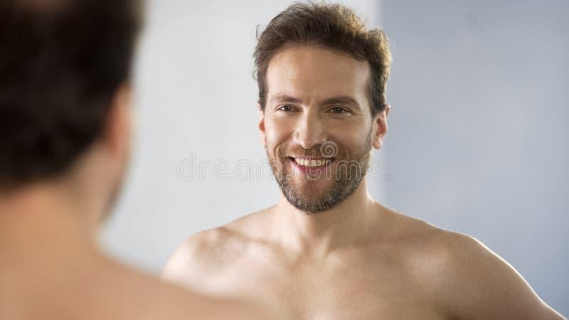 Glimlachende mens die op middelbare leeftijd admiringly zijn gedachtengang in spiegel bekijken royalty-vrije stock afbeeldingen