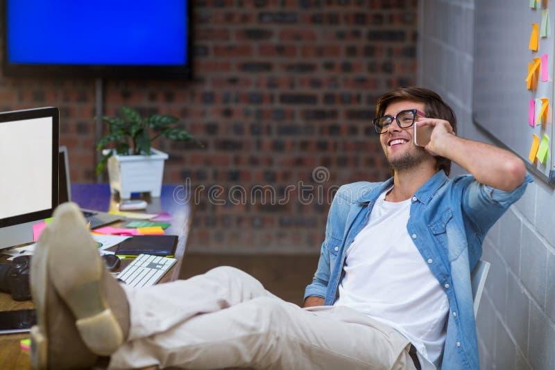 Glimlachende mens die op telefoon in bureau spreken royalty-vrije stock afbeeldingen