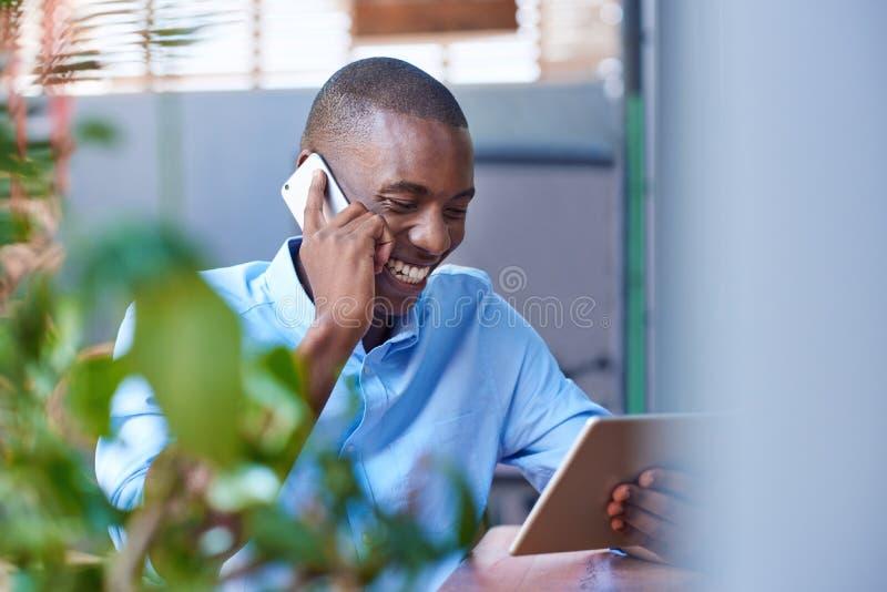 Glimlachende mens die op zijn cellphone bij een stoepkoffie spreken stock foto