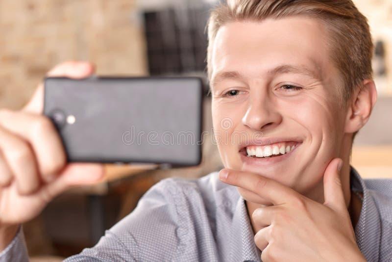 Glimlachende mens die selfie in koffie doen royalty-vrije stock fotografie