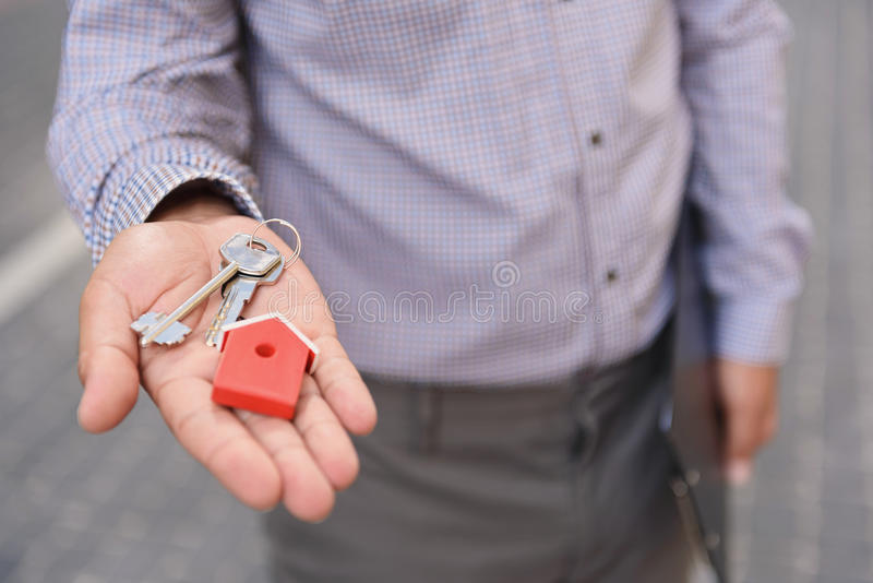 Glimlachende mens die sleutels steunen stock foto's