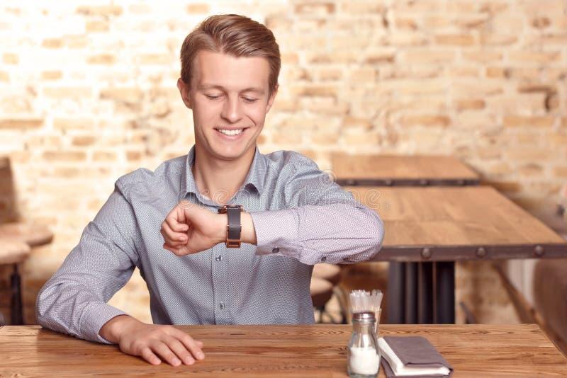 Glimlachende mens die tijd in koffie controleren stock fotografie