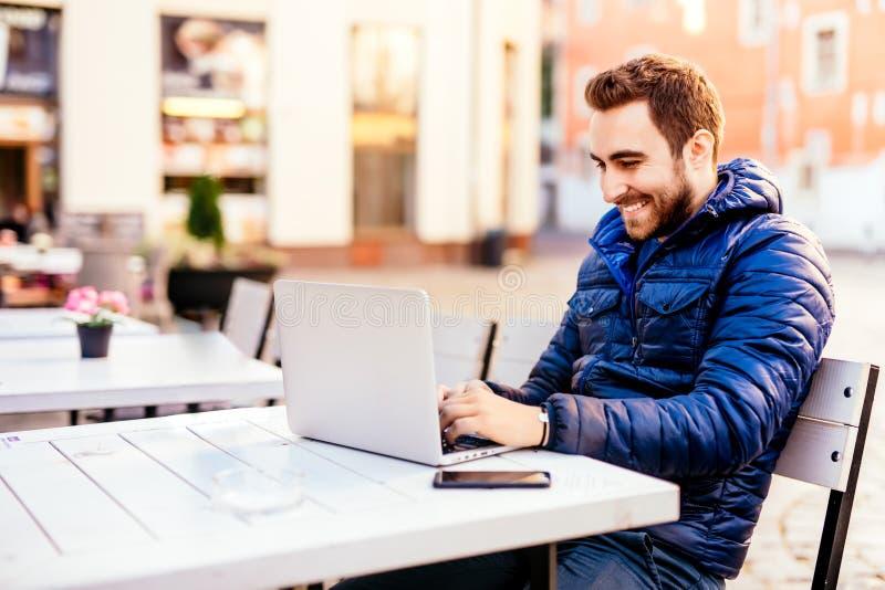 Glimlachende mens die van openluchtbureau werken Mens die jasje het typen op laptop op openluchtterras in stedelijk milieu dragen stock afbeelding