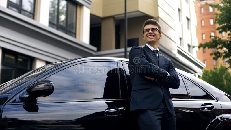 Glimlachende mens die zich dichtbij de auto van de premieklasse, het auto crediteren, lage rentevoet bevinden stock fotografie