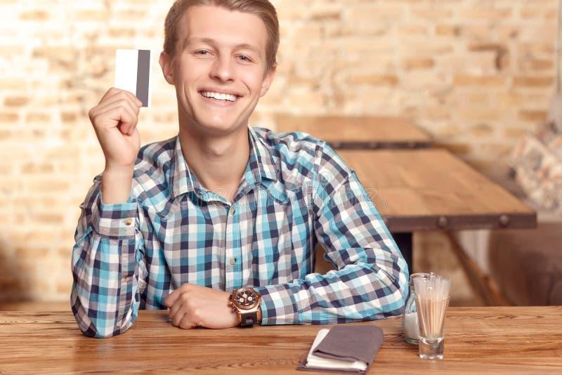 Glimlachende mens die zijn creditcard tonen royalty-vrije stock afbeelding
