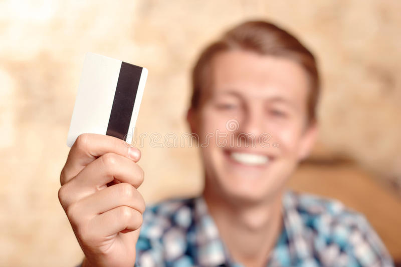 Glimlachende mens die zijn creditcard tonen royalty-vrije stock fotografie