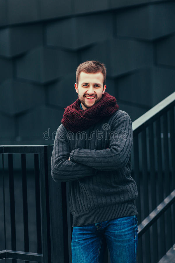 Glimlachende mens in een sweater en een sjaal stock fotografie