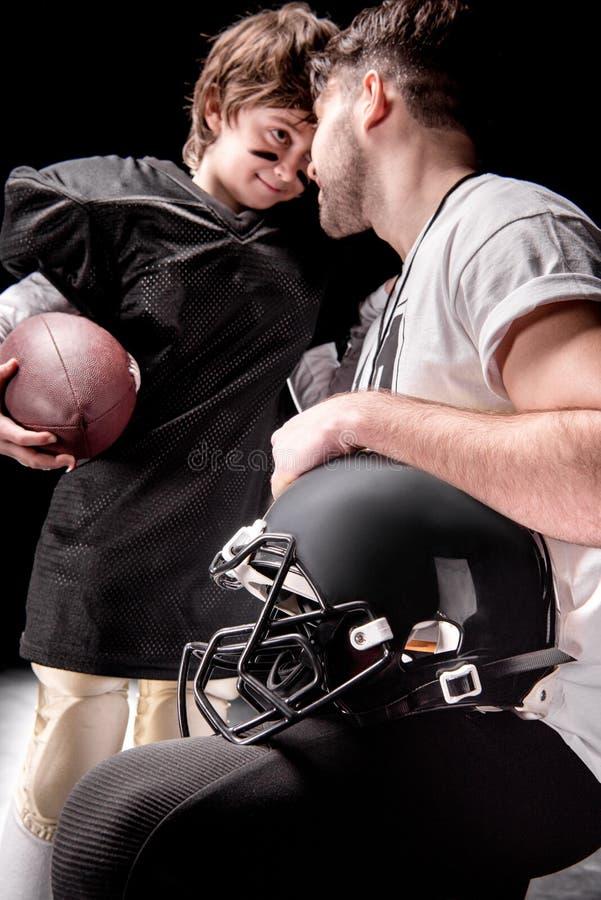 Glimlachende mens en jongen die met rugbybal elkaar bekijken stock foto