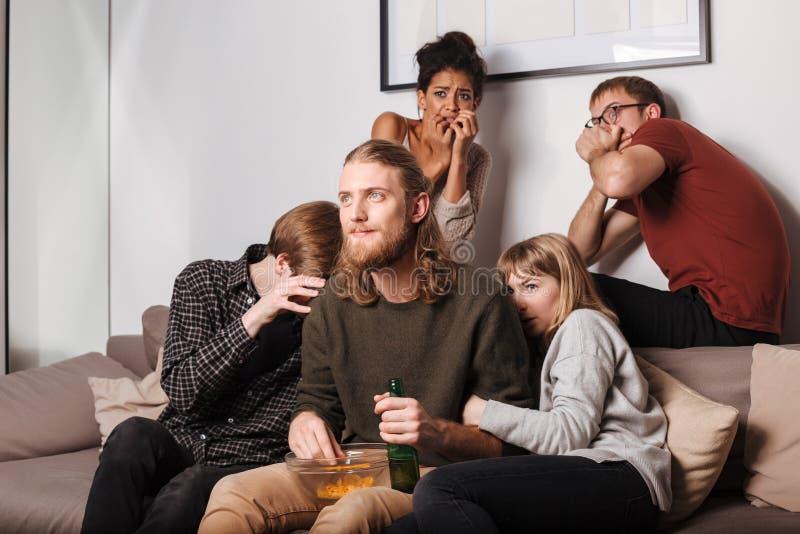 Glimlachende mens en zijn doen schrikken vrienden die op bank met spaanders en bier en het letten op verschrikkingsfilm zitten royalty-vrije stock afbeeldingen