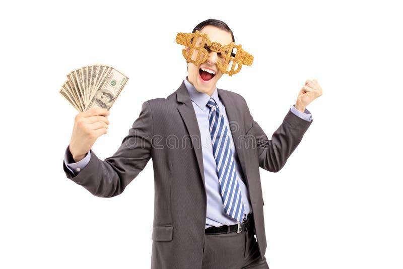 Glimlachende mens in kostuum die dollar glazen en het houden van dollars dragen stock foto's