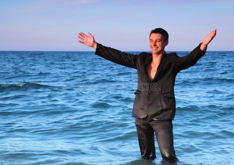 Glimlachende mens in kostuumtribunes in overzees royalty-vrije stock afbeelding