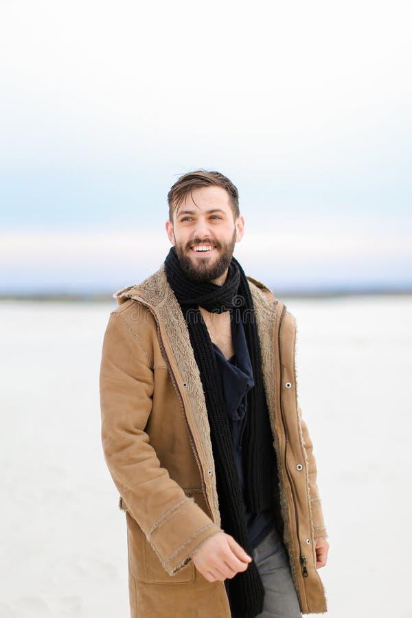 Glimlachende mens laag dragen en sjaal die op sneeuw op witte achtergrond lopen stock afbeeldingen