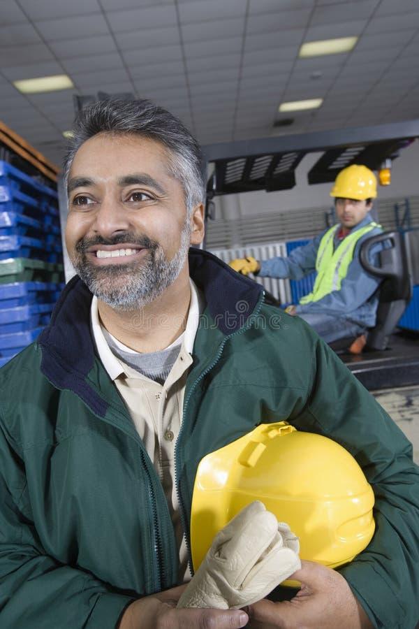 Glimlachende Mens met Collega erachter in Fabriek stock afbeeldingen
