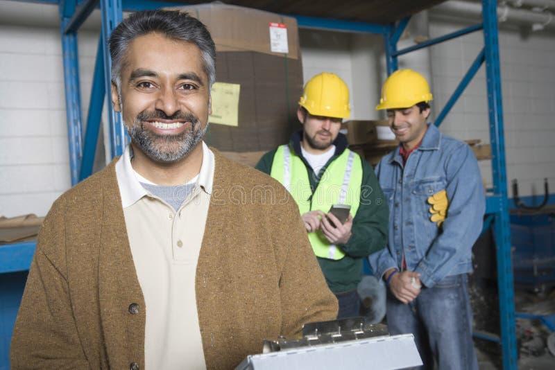 Glimlachende Mens met Collega's erachter in Fabriek stock foto's