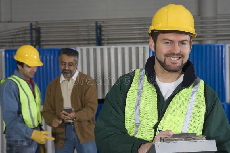 Glimlachende Mens met Collega's in Fabriek  royalty-vrije stock afbeelding