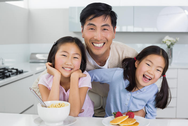 Glimlachende mens met gelukkige dochters die ontbijt in keuken hebben stock fotografie