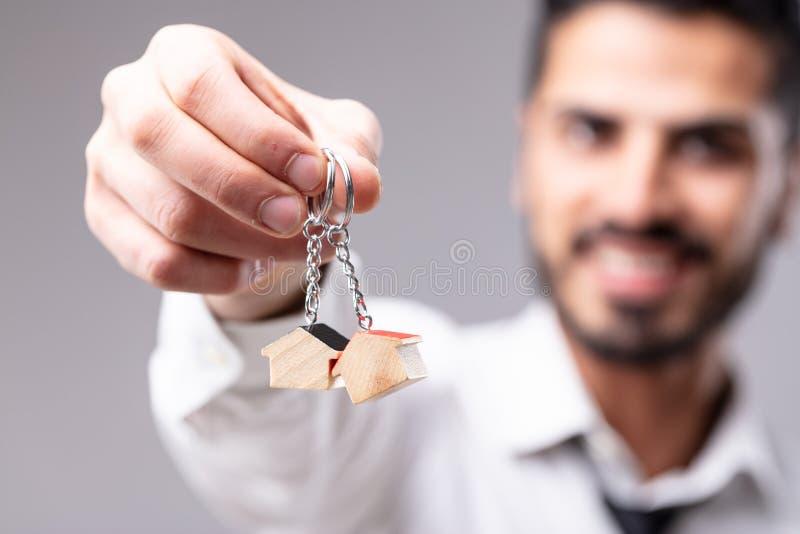 Glimlachende mens met sleutelringen in vorm van huis royalty-vrije stock fotografie